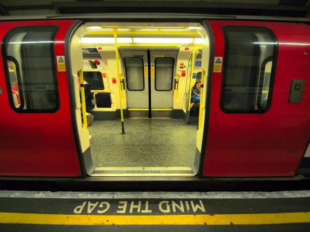 "London, United Kingdom - October 30, 2013: Detail in the Metro with train in station. The door are open in on person is written ""Mind the Gap"". Inside the train is strong light and door on other side is closed. On right is woman, passenger sleeping in train."